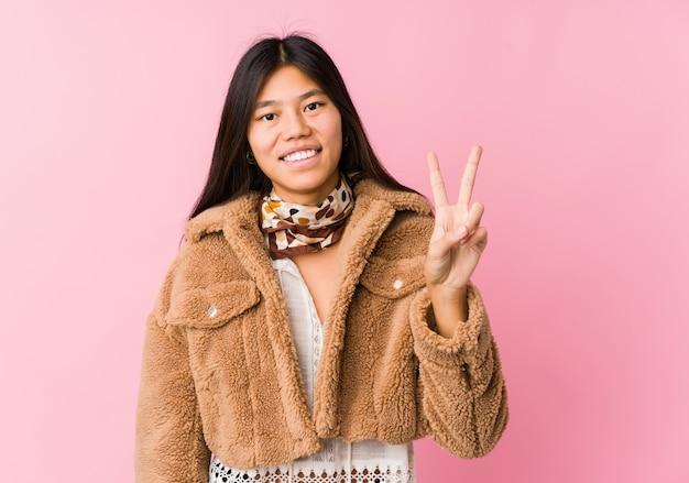 Молодая азиатская женщина показывая знак победы и широко усмехаясь. Premium Фотографии