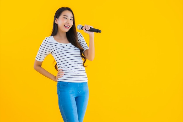 Young asian woman singing with microphone Free Photo