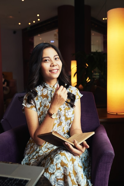 Young asian woman sitting in armchair in cafe with pen and journal Free Photo