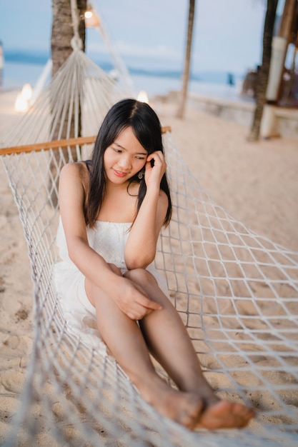Young asian woman sitting on hammock relax on beach, beautiful female happy relax near sea. Free Photo