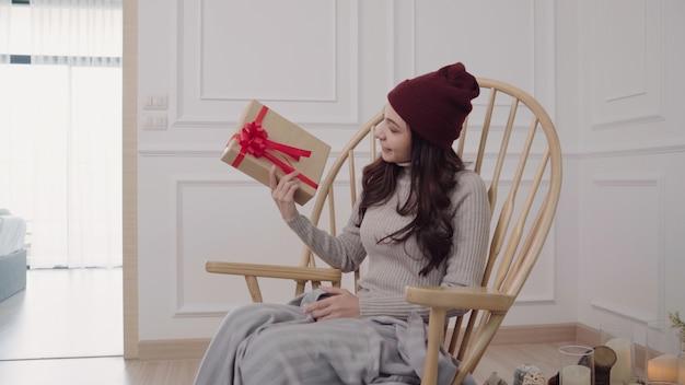 自宅で彼女のリビングルームに灰色の毛布に包まれた椅子に座っている若いアジア女性。 無料写真
