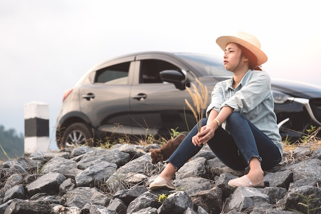 Young asian woman sitting with chihuahua dogs with black hatchback eco car. Premium Photo