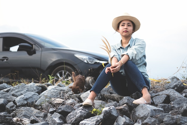 Young asian woman sitting with her dogs beside the road with black car and mile stone. Premium Photo