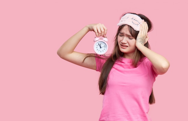 Young asian woman in sleeping eye mask yawning and holding alarm clock isolated on pink. sleepless night Premium Photo