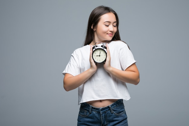 Молодая азиатская улыбка женщины с часами на сером фоне Бесплатные Фотографии