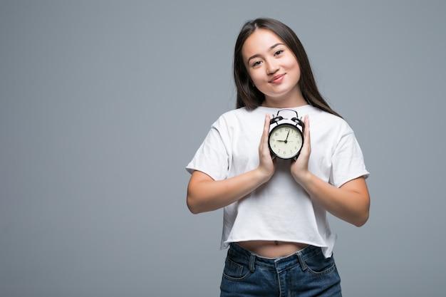 灰色の背景に分離された時計で若いアジア女性の笑顔 無料写真