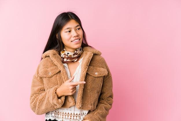 Молодая азиатская женщина усмехаясь и указывая в сторону, показывая что-то на пустом пространстве. Premium Фотографии