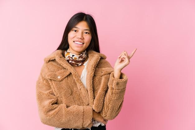 Молодая азиатская женщина усмехаясь жизнерадостно указывая с указательным пальцем прочь. Premium Фотографии