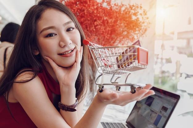 Молодая азиатская женщина усмехаясь держащ магазинную тележкау и кредитную карточку в руках пока счастливый ослабляет в кофейне Premium Фотографии