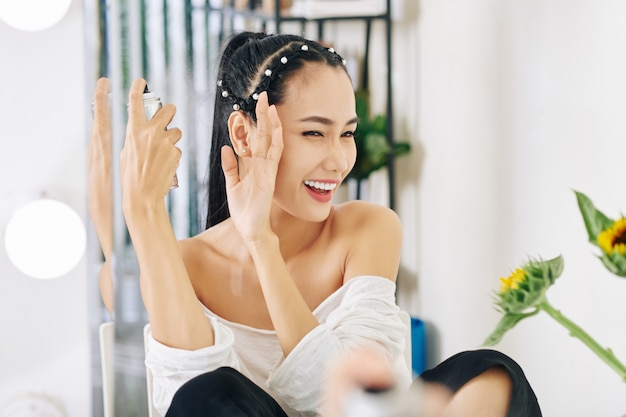 Молодая азиатская женщина прищуривает глаза и закрывает лицо рукой при нанесении лака для волос Premium Фотографии