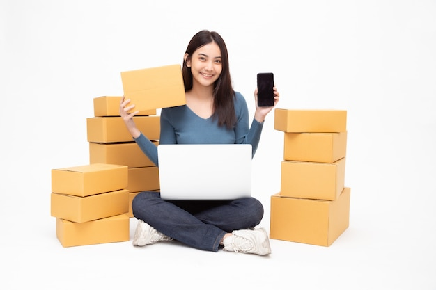 Young asian woman startup small business freelance holding parcel box, mobile phone and computer laptop and sitting on floor isolated, online marketing packing box delivery concept Premium Photo
