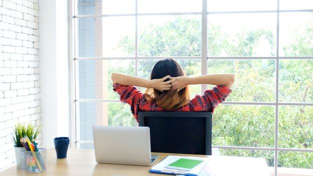 彼女の机のホームオフィスでラップトップコンピューターでの作業中に体を伸ばして若いアジア女性 Premium写真