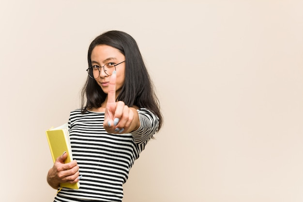 指でナンバーワンを示す本を保持している若いアジア女性学生。 Premium写真