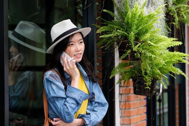 市屋外バックグラウンドで携帯電話を取る若いアジア女性 Premium写真