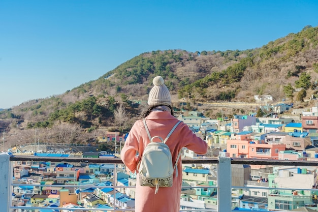 Young asian woman traveler with backpack traveling into the gamcheon culture village located at busan, south korea Premium Photo