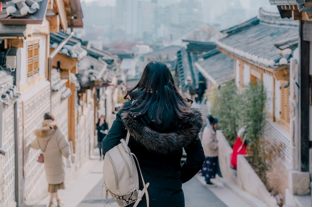 Young asian woman traveler with backpack traveling into the traditional korean style architecture Premium Photo