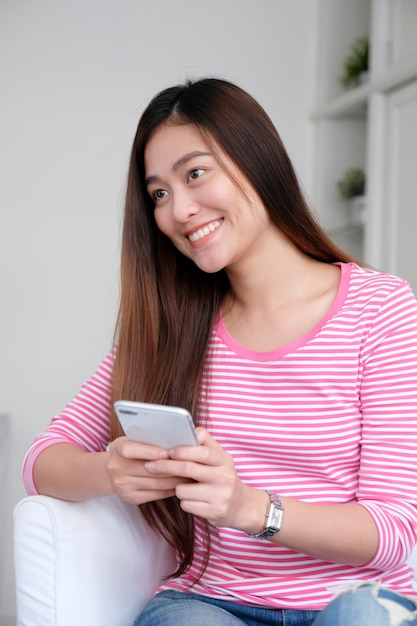 Young asian woman using smartphone in white room background, Premium Photo