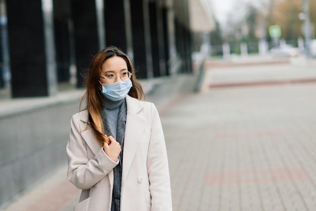 フェイスマスクを身に着けている若いアジアの女性が国内の通りに立っています。新しい正常なcovid-19の流行 Premium写真