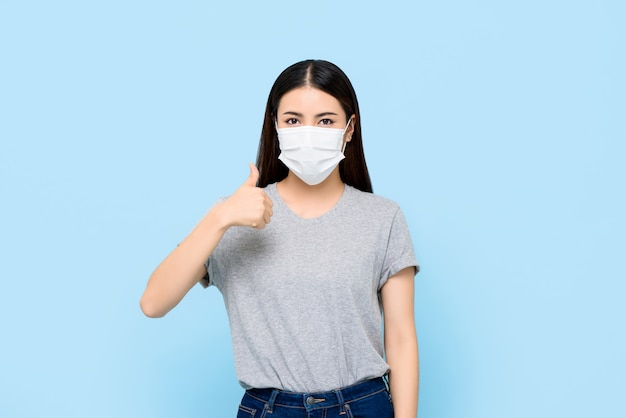 Young asian woman wearing face mask protecting coronavirus and allergies giving thumbs up isolated on light blue wall Premium Photo