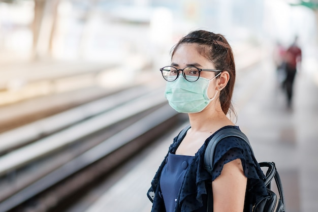 Young asian woman wearing surgical face mask against novel ...