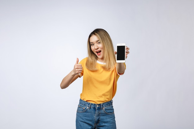 Young asian woman wearing in yellow shirt is showing thumb up sign on white background Premium Photo