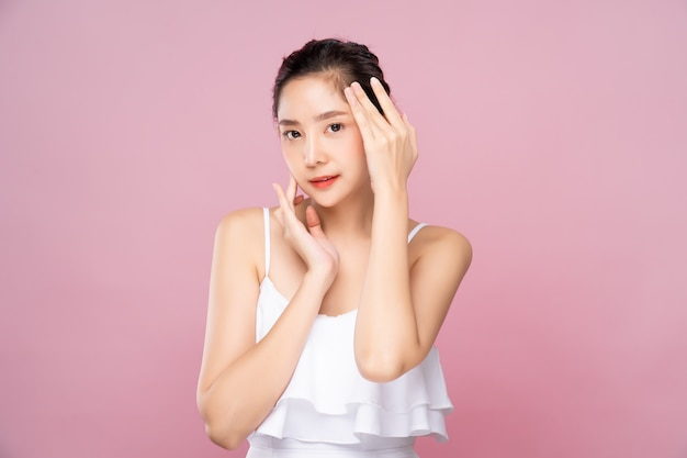 Young asian woman with clean fresh white skin touching her own face softly in beauty pose Premium Photo