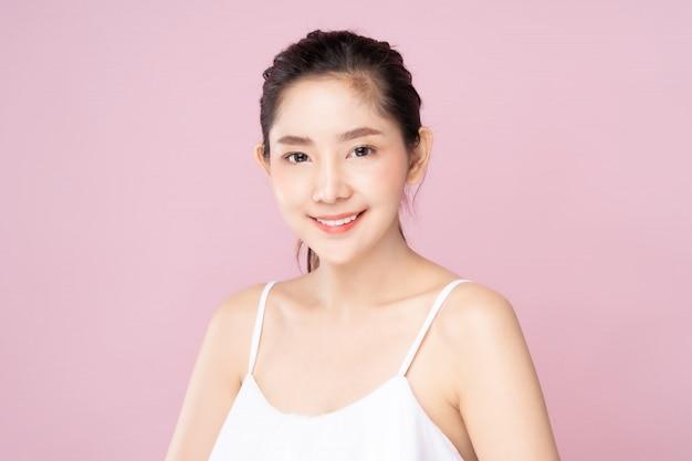 美容ポーズでにこやかな顔と清潔で新鮮な白い肌を持つ若いアジア女性 Premium写真