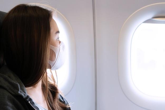 Молодая азиатская женщина с медицинской маской, сидя на самолете. концепция защиты от коронавируса covid-19. Premium Фотографии