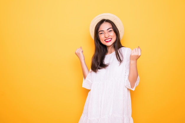 Young asian woman with winning gesture isolated on yellow wall Free Photo
