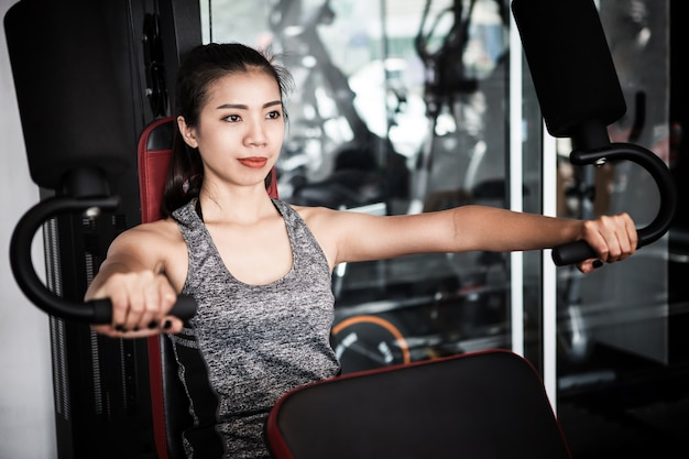 Young asian woman working out on an exercise machine Premium Photo