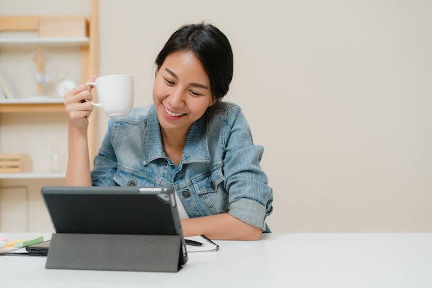 Young asian woman working using tablet checking social media and drinking coffee while relax on desk in living room at home. Free Photo