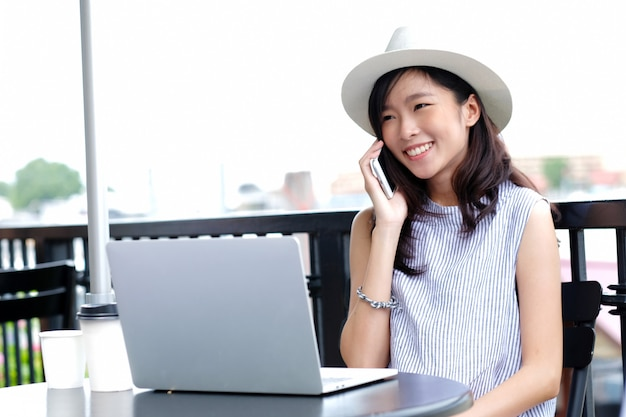 Young asian woman working with laptop computer and talking phone at nature park background Premium Photo