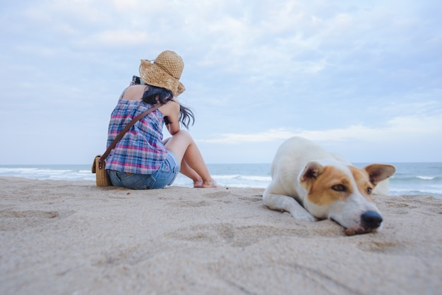 Young asian women sit sadly at the beach by the sea with a dog, sitting on the beach in the background Premium Photo