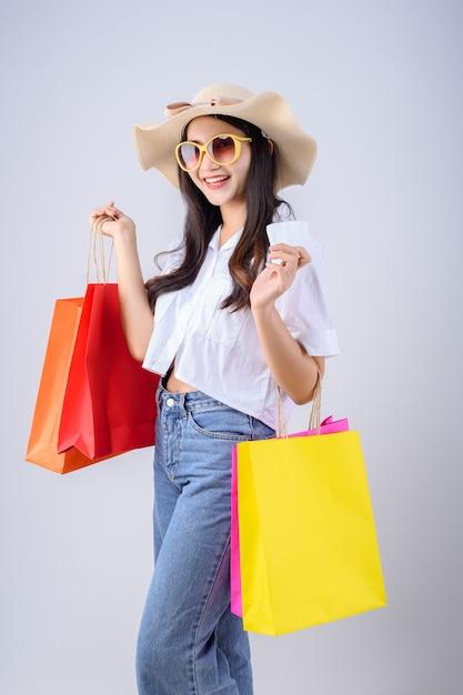 안경과 모자를 착용하는 젊은 아시아 여성 흰색 배경에 많은 다채로운 쇼핑 가방과 함께 법안을 보유하고 있습니다. 프리미엄 사진