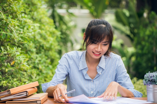 Young asian women writing homework on desk in outdoors, woman working with happy emotion concept. vintage effect style pictures. Free Photo