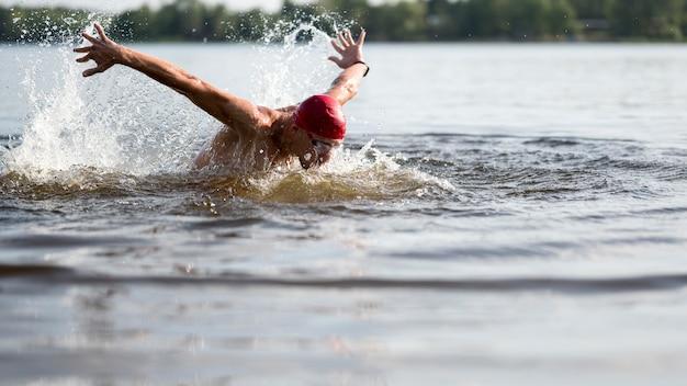 湖で泳いでいる若い選手 無料写真