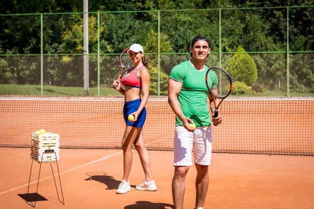 Молодая спортивная пара, играя в теннис на корте. Premium Фотографии