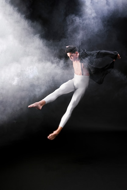 Young athletic man jumping and dancing near smoke against black background Free Photo