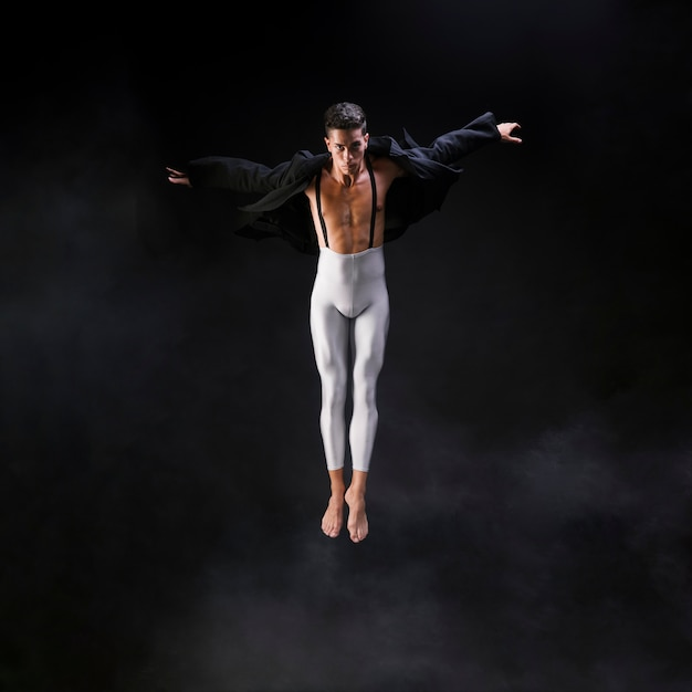Young athletic man jumping with extended hands near smoke against black background Free Photo