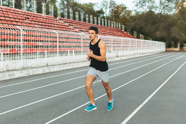 Young athletic man running on the stadium in the morning Free Photo