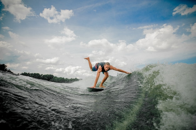 Young and athletic man wakesurfing on the board down the river against the sky Premium Photo