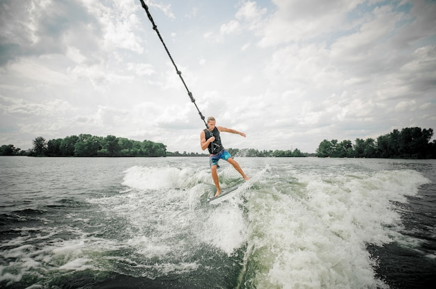 Young and athletic man wakesurfing on the board holding a cable Premium Photo