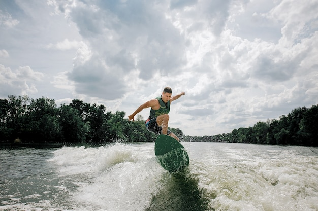 Young and athletic man wakesurfing on the board Premium Photo