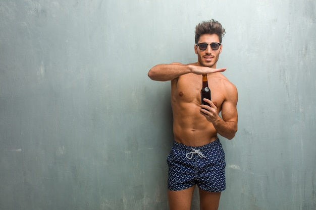 Young athletic man wearing a swimsuit against a grunge wall tired and bored, making a timeout gesture Premium Photo