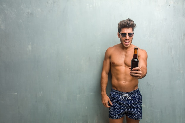 Young athletic man wearing a swimsuit against a grunge wall very angry and upset Premium Photo