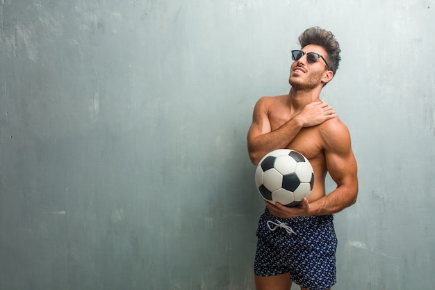 Young athletic man wearing a swimsuit against a grunge wall with back pain due to work stress, tired and astute Premium Photo