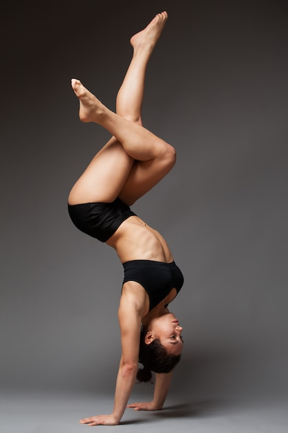 Young athletic woman in a black top and shorts performing handstand Premium Photo