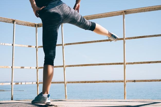 Молодая спортивная женщина, делающая ногу, растягивающуюся на пляже утром Premium Фотографии