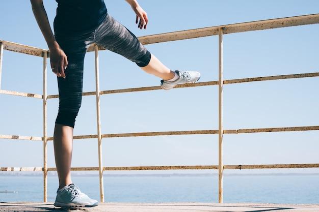Молодая спортивная женщина делает растяжку на пляже по утрам Premium Фотографии