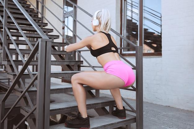 Una giovane donna atletica in camicia e cuffie bianche che risolvono ascoltando la musica su una scala all'aperto. fare squat e passi. concetto di stile di vita sano, sport, attività, perdita di peso. Foto Gratuite